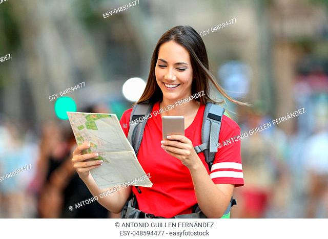 Front view of a happy teen tourist searching location online walking on the street