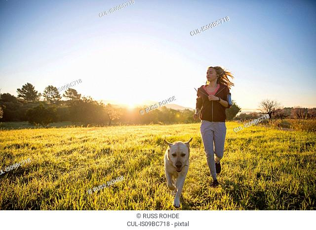 Young woman running across field, with pet dog