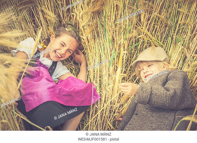 Germany, Saxony, two children lying in a grain field having fun