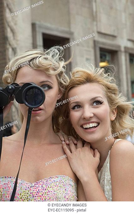Woman with binoculars sightseeing with friend