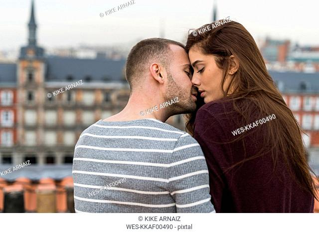 Amorous couple sitting on rooftop, kissing and ambracing
