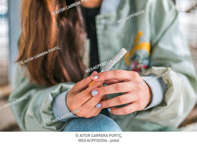 Woman's hands rolling a Marihuana joint, close-up