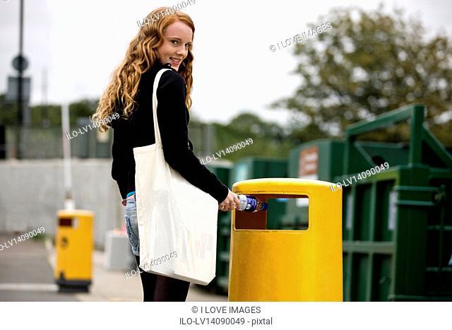 A teenage girl putting a plastic bottle into a rubbish bin