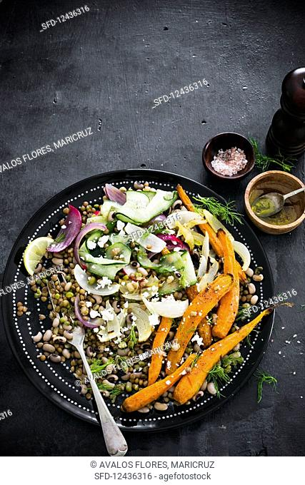 Lentils and beans vegan salad with roasted and fresh vegetables and crumbled vegan feta