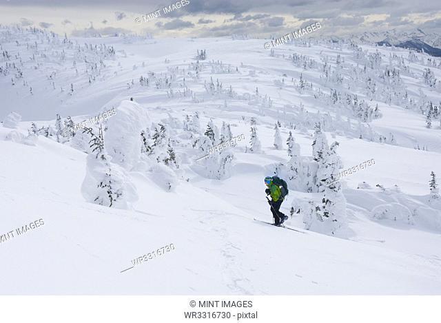 Caucasian snowshoer walking up snowy hillside