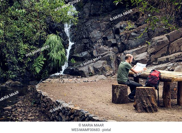 Hiker taking a break at rest area, Barranco el Cedro, La Gomera, Canary Islands, Spain