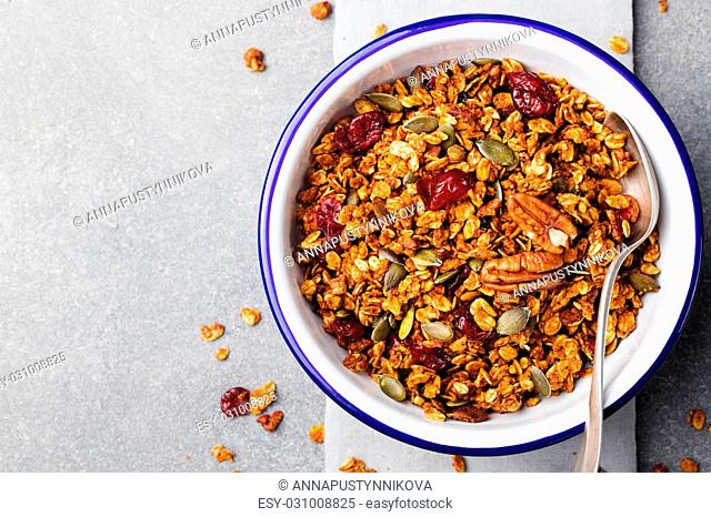 Healthy breakfast. Fresh granola, muesli with pumpkin,pecan nuts,cranberries and maple syrup in white bowl Copy space. Top view
