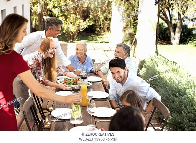 Happy family preparing lunch on garden table
