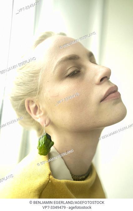 young apathetic woman wearing earring made of raw zucchini
