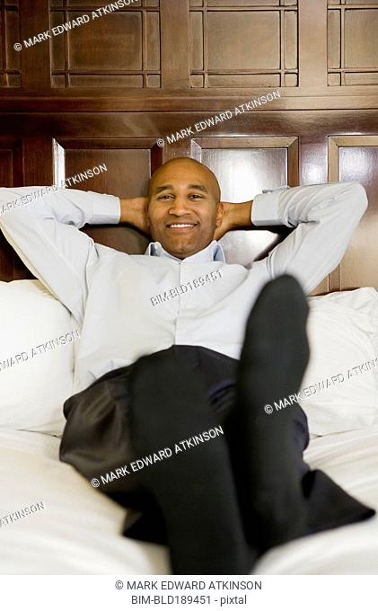 African businessman relaxing on bed