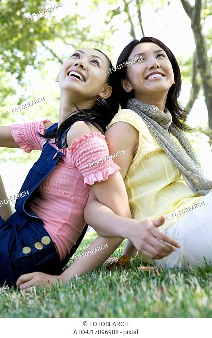 Young women sitting back to back on lawn, smiling and looking up
