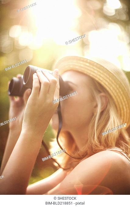 Caucasian woman looking through binoculars