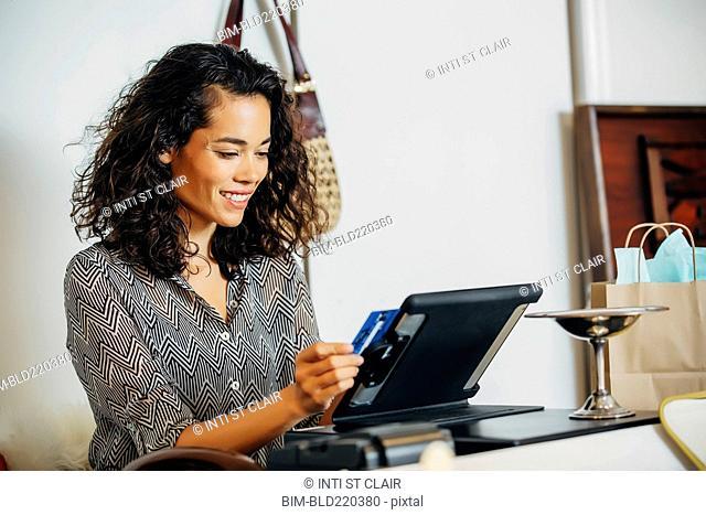 Mixed race clerk swiping credit card at register