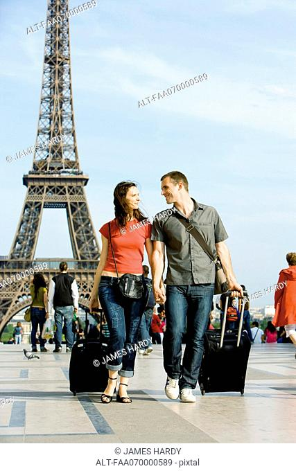 Couple walking with rolling luggage near Eiffel Tower, Paris, France