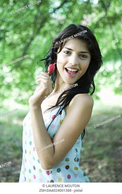Young woman holding up radish, smiling at camera