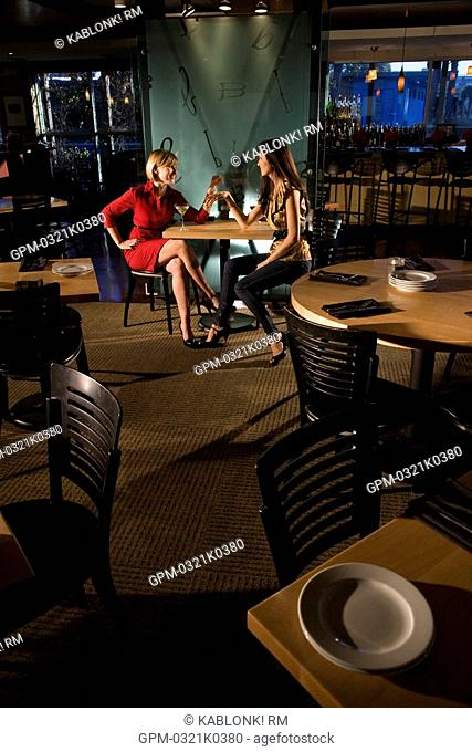 Two young women sitting in restaurant having drinks