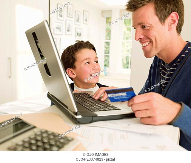 Father and son shopping online with credit card