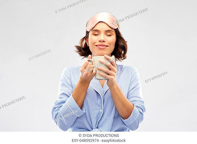 woman in pajama and sleeping mask drinking coffee