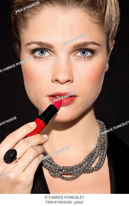 Portrait of a beautiful woman applying lipstick