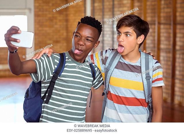 Happy schoolboys taking selfie on mobile phone in campus