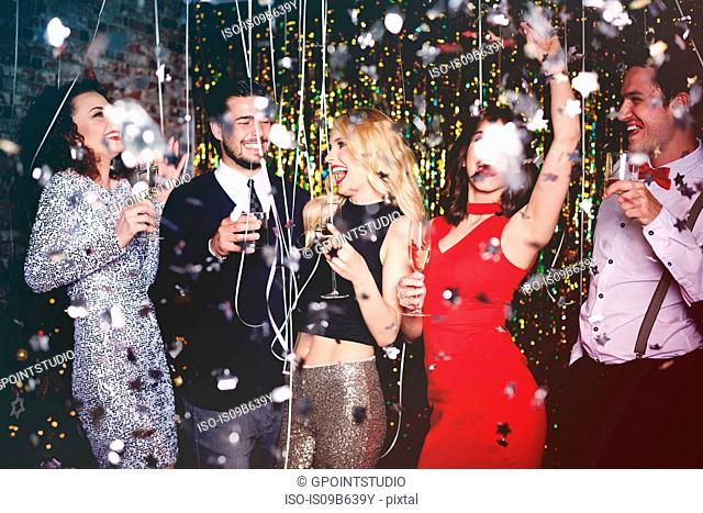 Group of people dancing and having fun at party, glitter falling through air