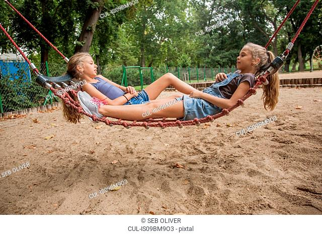 Girls relaxing on net swing