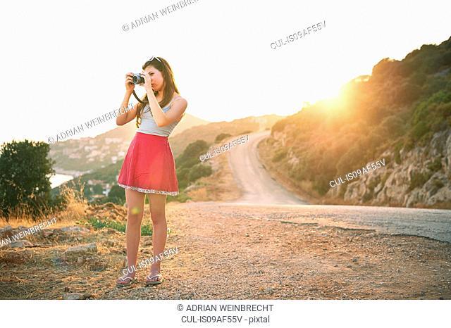 Girl taking photographs at sunset, Kas, Turkey