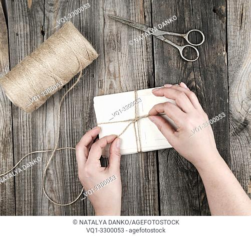 female hand bandages stack of cards with brown rope on a gray wooden table, top view