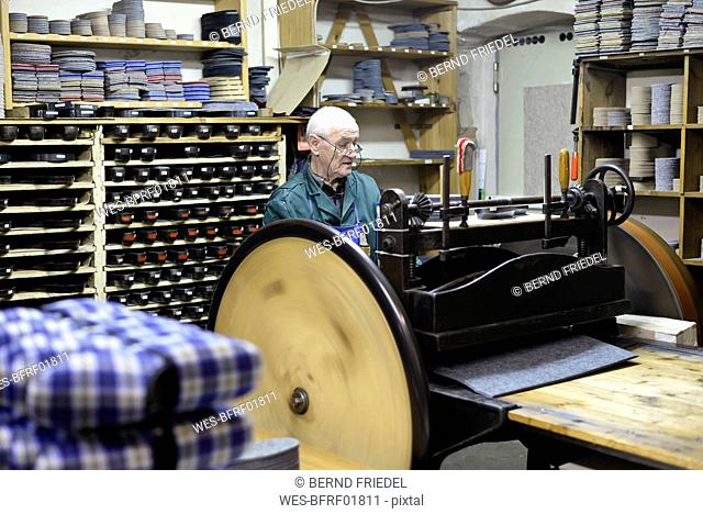 Senior shoemaker working with old-fashioned punching machine in workshop