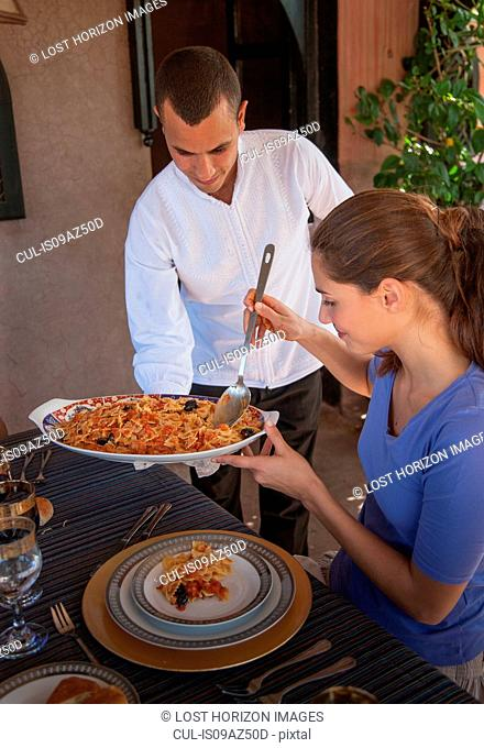 Waiter offering woman food on serving dish, Marrakesh, Morocco