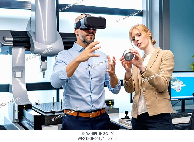 Businessman and businesswoman withVR glasses and workpiece in factory
