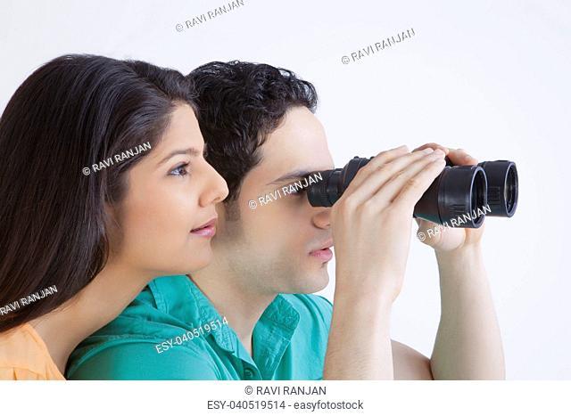 Young man and woman looking through binoculars