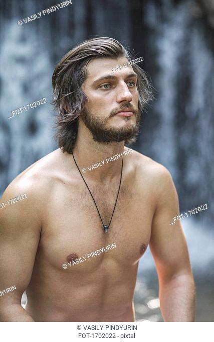 Thoughtful shirtless young man looking away while standing against waterfall at forest