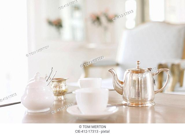 Teacups and silver teapot on table