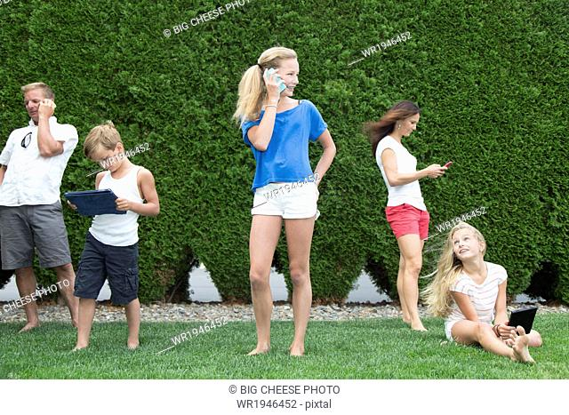 Family of five all using technology outdoors