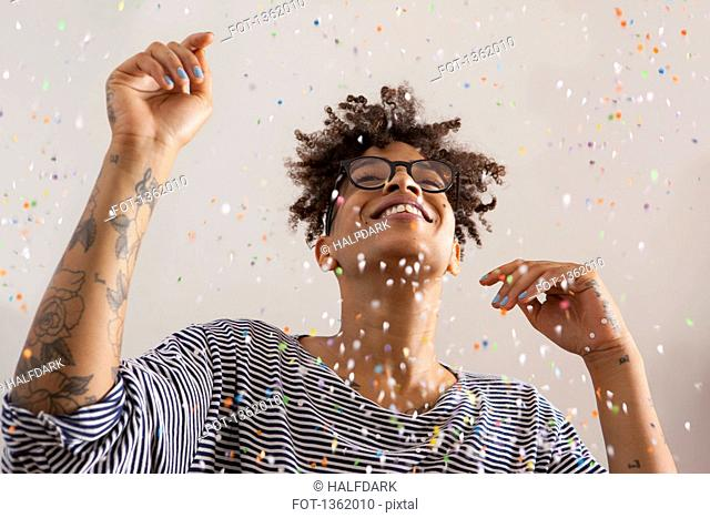 Happy young woman enjoying confetti falling on her over gray background
