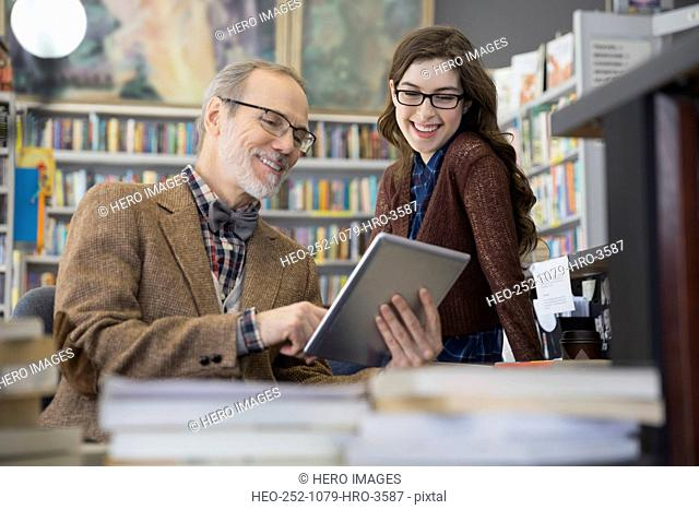 Bookstore owner and worker using digital tablet