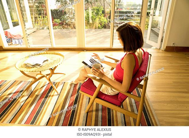 Businesswoman using touchscreen on digital tablet in living room