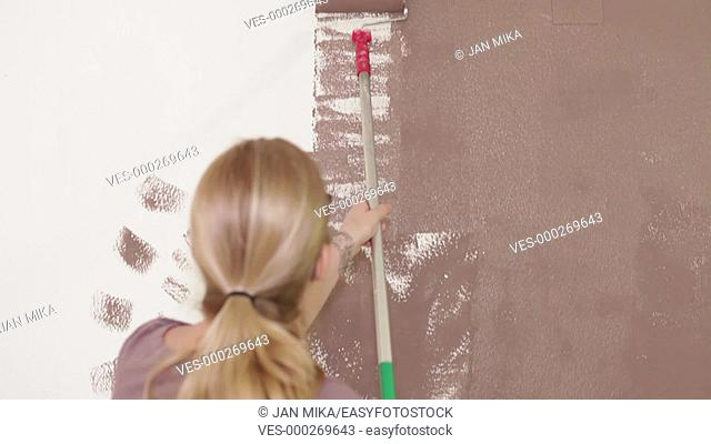 Woman with paint roller painting white wall at interior using brown color