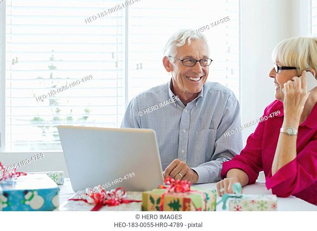 Senior couple using mobile phone and laptop at Christmas time