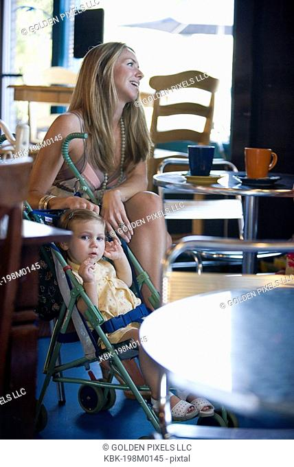 Attractive young woman with her baby in a cafi