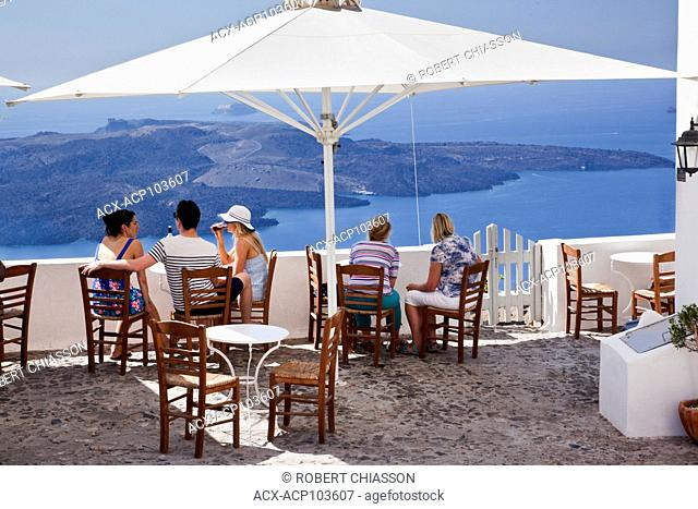Terrace of To Kafenio Wine Bar and Cafe offering a view of the South Aegean Sea (locally referred to as the Caldera) and the volcanic island of Nea Kameni (New...