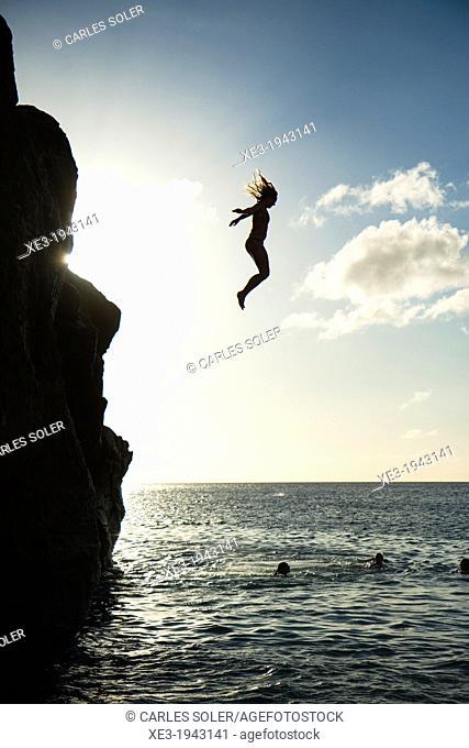 Girl jumping into water, Waimea Bay, Oahu, Hawaii