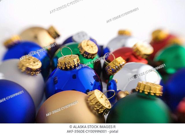 Colorful Christmas tree bulb ornaments piled together on white background studio portrait