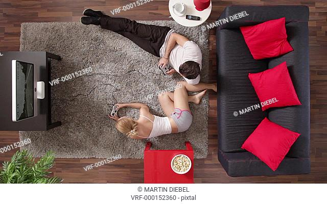 MS, couple playing a video game, woman winning, overhead view