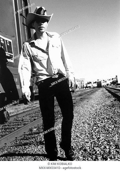 Cowboy standing on train tracks with train in background