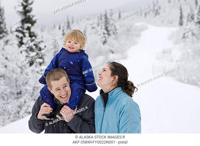 Couple take young son for an outdoor walk during Winter in Pedro Bay, Alaska