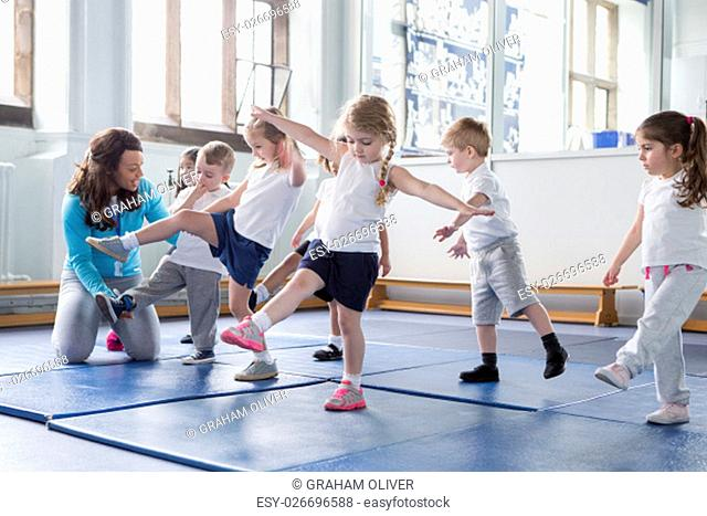 Nursery teacher helping one of her students during a physical education lesson