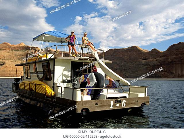 A HOUSE BOAT enters REFLECTION CANYON, one of 96 arms of LAKE POWELL NATIONAL RECREATION AREA - UTAH