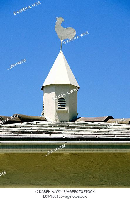 Weather vane of a rooster atop tile roof of house, against blue sky